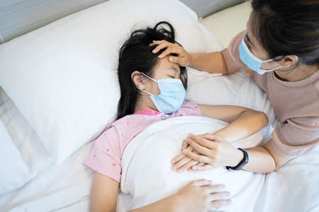 Loving mother is visiting and caring her sick daughter lying in bed,asian woman wearing medical mask holding hand,touching the forehead of child girl patient,checking the body temperature with hand Standard-Bild