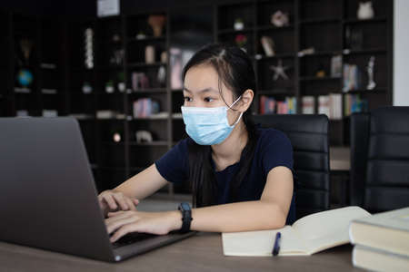 Distance learning online education with computer,schoolgirl wearing protective mask studying online class,student chatting with teacher on laptop computer at home during COVID-19 pandemic,new normal