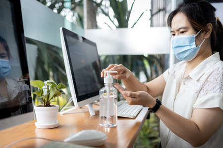 Asian woman cleaning hands with hand sanitizer after use and before starting work on computer at office,avoid contaminating with Coronavirus,wash hands frequently,new normal conditions under COVID-19