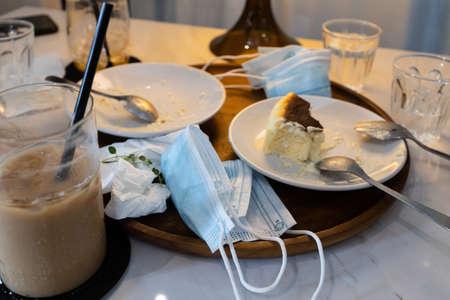 Infectious waste of medical masks,scraps of food,tissues on plates and used protective face masks left in a tray,leftover food and dirty dishes,garbage on the dining table in restaurant,Stop littering