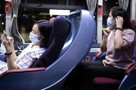 Asian people wearing medical protective masks while traveling in public transportation,safety in new normal conditions under COVID-19,stronger together,stop the infection and spreading of Coronavirus