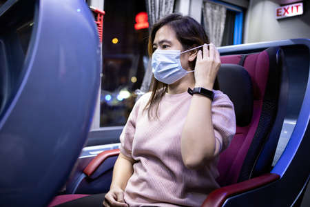 Asian female passenger wearing protective mask while traveling in the public transport by bus,Coronavirus pandemic,protection in public transportation,safety in new normal conditions under COVID-19 免版税图像