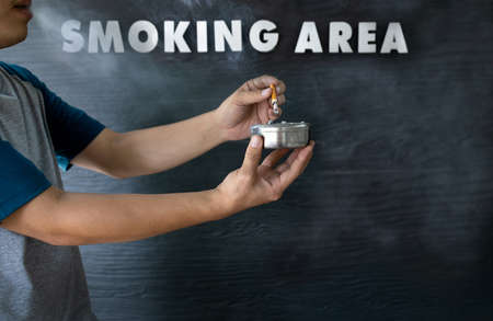 Hands of asian man holding a ashtray and cigarette butts,smoker blowing smoke out his mouth while smoking cigarette in smoking area zone,designated smoking area text on the black wood background