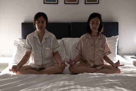 Happy asian people meditating in yoga pose,sit in lotus position on the bed at home,healthy child daughter and mother are practicing yoga exercise together,relaxation,calmness,meditation,health care
