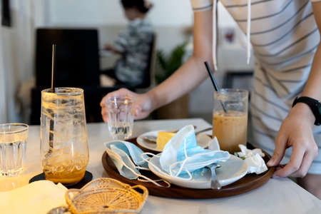 Hand of female waitress holding a tray with scraps of food,leftover food,dirty dishes,tissues and used protective face masks left on plates,girl cleaning the table in a restaurant,concept of littering