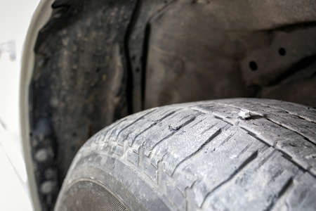 Close up of sharp metal screw puncturing into a car tire,flat tire,car tire leak by button head needle nut on the street,waiting for repair,problems of motorists on the road,traveling concept