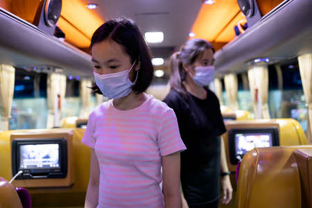 Asian passengers in medical protective masks while traveling by public bus,safety,travel in new normal conditions under COVID-19 pandemic,tourists wearing face masks for protection from Coronavirus 免版税图像