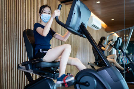 Asian child girl in a protective mask sitting on the spinning bicycle,smiling female working out by recumbent bike in the gym,physically fit and healthy,wear a face mask while exercise in new normal