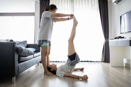 Happy asian child girl workout with mother in living room at home,doing leg raises exercise,woman and daughter have fun,laugh,enjoy exercising,physically fit and healthy lifestyle,health care concept 免版税图像