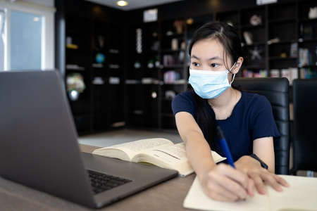 Asian student wearing protective mask,taking notes from laptop computer and textbooks in library at school,writing do homework,concentrated child girl make notes in the book prepare for test or exam