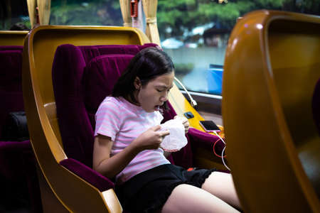 Unhappy asian child girl about to throw up,puking,motion sickness symptoms, holding sick bag,sad female teenage vomiting in a bus suffers from motion sickness,feels dizziness and nausea from carsick