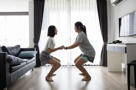 Happy asian woman and child girl holding hands together while workout,doing sumo squat exercise at home,have fun,laugh,enjoy on the weekend,family leisure activities,fitness,healthy lifestyle concept