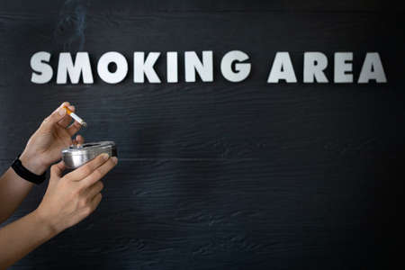Hands of asian woman holding a ashtray and cigarette,people extinguishing a cigarette in smoking area zone,designated smoking area text on black background,unhealthy lifestyle,quit smoking concept 免版税图像