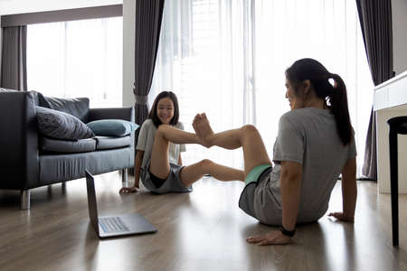 Exercise activities with family,Happy smiling woman doing abdominal workout with child girl having fun,laugh,enjoy,Healthy asian people doing bicycle crunches pose in the house,health care concept