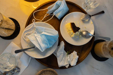 Infectious waste of medical masks,scraps of food and used protective face masks left on plates in restaurant during the Coronavirus,COVID-19 pandemic,dirty dish,garbage on the table,Stop littering