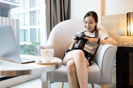 Happy smiling asian teenager girl watching photos from travel on digital camera while sitting on armchair in hotel room on summer vacations,female traveler checking picture photos after taking a photo