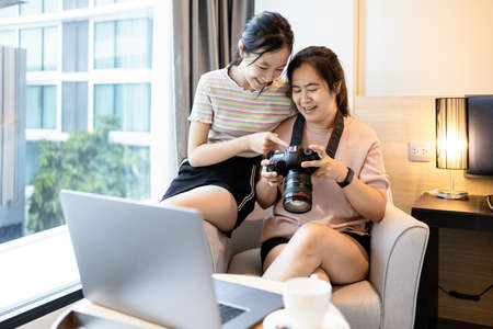 Happy smiling mother and child daughter watching picture photos from travel on camera together at hotel room,trip on holidays,asian woman and girl laughing having fun,lifestyle,summer vacation concept