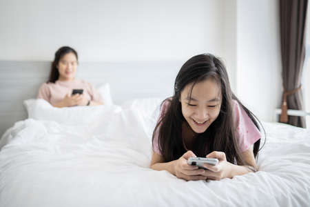Asian child daughter using mobile phone typing text message,chatting to her mother while sit in bed together at home,addicted to a cell phone,social online communication,problems of internet addiction