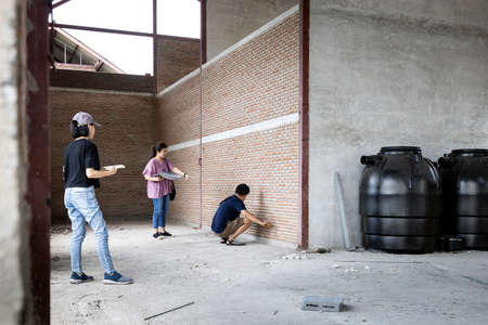Asian family visiting their new home being built,inspect the house structure,man measuring size of the room on the brick walls,building improvement,plan to expand,renovation and construction concept Standard-Bild