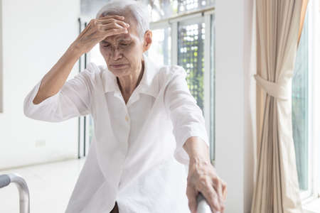 Exhausted asian senior woman is touching her head with hand,symptoms of vertigo illness,loss balance dizzy,meniere's disease,feel unwell faint,sick elderly people having a  headache,health problem Standard-Bild