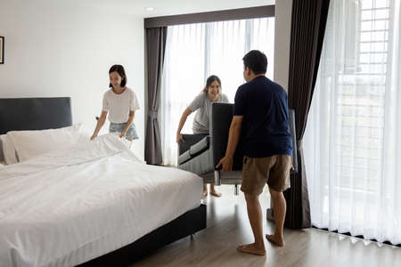 Asian family clean and organizing the room after renovating,father and mother movers carrying sofa,child girl making bed,enjoy the new bedroom,stay at home during the Coronavirus COVID-19 pandemic