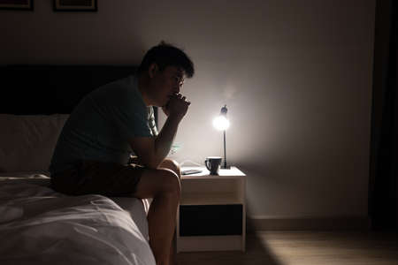 Stressed disappointed asian man thinking about life,family,work,financial and economic problems from Coronavirus COVID-19,unemployed male sit alone,contemplating with his hands at the chin in the bed