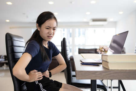 Asian girl suffering from abdominal pain,chronic inflammation of stomach or gastritis caused by stress,overwork and haven't eaten lunch,touch belly with her hands,stomach ache while excessive work Archivio Fotografico
