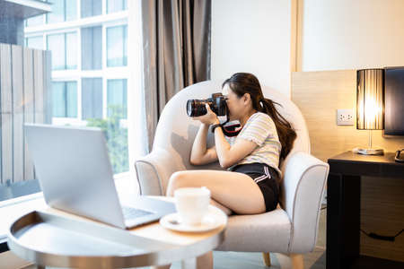 Asian female tourist taking a picture,setting and testing photo with new dslr camera during planning trip in hotel room on holidays,hobby and leisure activity,lifestyle,summer vacation concept Standard-Bild