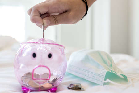 Closeup,hand of Asian child girl put coin through the hole in pink piggy bank with medical protective mask,saving money for health insurance,health care costs,money saving plan for future investment Standard-Bild