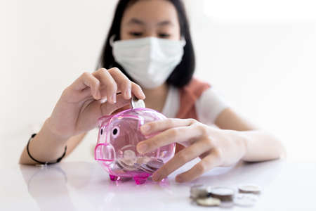 Asian child girl wear protective mask,put coin through the hole in piggy bank,try to save up more money for health care cost,insurance for Coronavirus,financial,investment,money saving plan concept Archivio Fotografico
