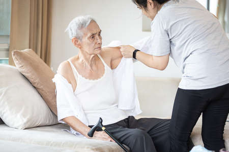 Asian female caregiver taking care of helping elderly patient get dressed,wearing clothes or undressing for senior mother,depressed old woman with amnesia,loss of memory,daily life in a nursing home