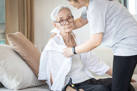 Assisting in dressing,asian female caregiver taking care of helping senior woman get dress,chang clothes for old mother,Alzheimer's elderly patient sit on the sofa at home,preparing go to the hospital Standard-Bild