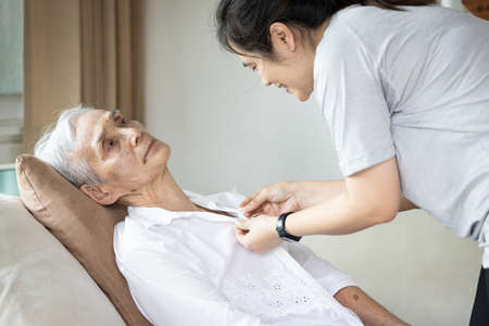 Asian female caregiver taking care of helping elderly patient get dressed,button on the shirt or changing clothes for a paralyzed person,senior woman with paralysis of limbs,body or muscles weakness