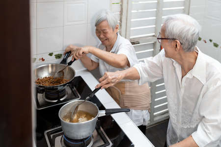 Happy smiling asian senior women are cooking stir-fried pork with basil and soup,elderly siblings enjoying preparing meal Thai food in kitchen at home,healthy food,concoction,family lifestyle concept Archivio Fotografico