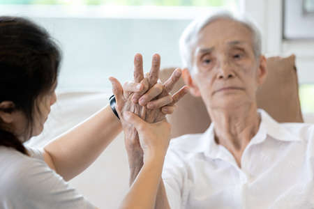 Elderly female patient suffer from numbing pain in hand,arthritis,tendon inflammation,stiffness of the joints,asian senior woman get a palm finger massage to treat beriberi,numbness fingertip concept Standard-Bild