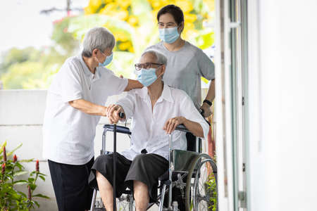 Happy asian senior woman wearing protective mask sit in wheelchair with best friend visit to the home during COVID-19,Coronavirus pandemic,old elderly people embracing holding hands warm relations