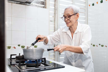 Old elderly people cooking vegetables soup,mixing and heating the ingredients,healthy food,good cook,asian senior woman standing by the stove in the kitchen at home,preparing food,concoction concept