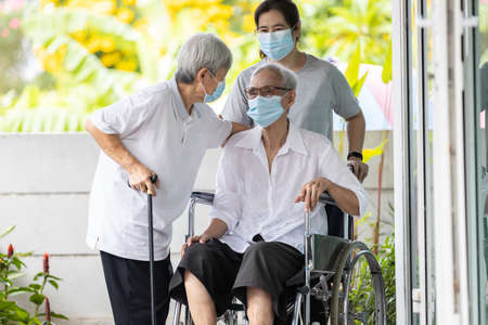 Happy asian elderly woman wearing medical mask sit in wheelchair with female caregiver,best friend or her family visit to the home during COVID-19,Coronavirus pandemic,senior people embracing enjoy