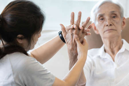 Elderly female patient suffer from numbing pain in hand,arthritis,tendon inflammation,stiffness of the joints,asian senior woman get a palm finger massage to treat beriberi,numbness fingertip concept Archivio Fotografico