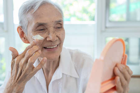 Happy smiling asian senior woman apply sunscreen lotion on the cheek,protect her beautiful face,old elderly using skin care product for sensitive skin,sun block day cream on facial skin in sunny day Archivio Fotografico