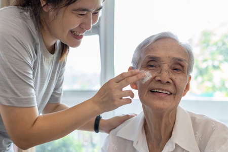Female caregiver assisting to apply sunscreen lotion on the face of senior woman,granddaughter using skin care cream for elderly sensitive skin,happy smiling grandmother with sun block on facial skin
