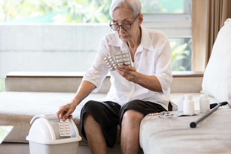 Elderly people is checking expiration date or deterioration of medication before use in the treatment,senior woman reading pill label before taking of medicine and throwing expired drug into the trash Archivio Fotografico