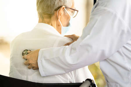 Close up of a female doctor's hand using stethoscope listening to heartbeat and breath of senior patient,physician checking heart and lungs of senior woman at the back of the body with a stethoscope