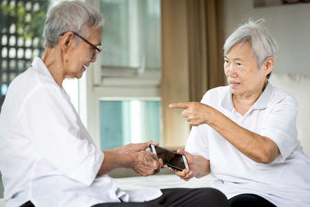 Senior women fighting or conflict for smartphone,sibling in old age or two elderly pulling apart mobile phone,quarreling,arguing,addicted to online movies,social networking,internet addiction problems