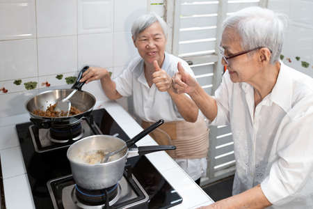 Happy smiling asian senior women showing thumbs up hand sign while cooking delicious stuffed bitter gourd in clear soup,old elderly enjoying preparing meal Thai food in kitchen at house,healthy food