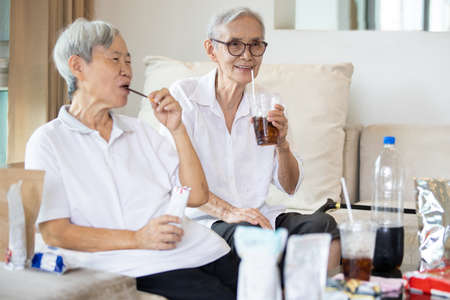 Two elderly people drinking soft drink,eat junk food,bottle of soda drink and snacks on the table at home,asian senior women holding glass of cola with ice,food consumption and eating behavior concept Standard-Bild