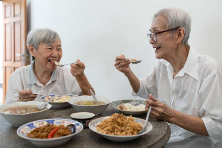Happy smiling asian senior women eating Thai food,sitting at dining table in the house,old people talking and enjoy during breakfast,eat with rice,local cuisine,health care,healthy food of elderly