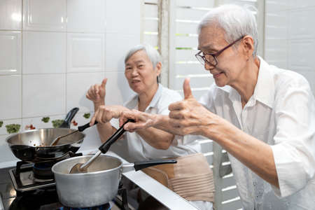 Happy smiling asian senior women thumb up while cooking vegetables clear soup,elderly siblings enjoying preparing meal Thai food in kitchen at house,healthy food,concoction,family lifestyle concept