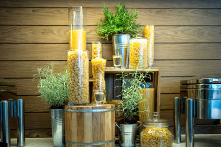 Variety of raw dry pasta rigatoni, fusilli, penne, fettuccine, spaghetti, linguine and macaroni,Italian pasta in glass jars,set of many different pasta types in the kitchen,dining room or restaurant