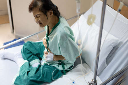 Asian elderly woman with a stomach ache holding her belly,abdominal disease,intestinal infection problems,acute enteritis,cancer or tumors,patient with saline solution during treatment in a hospital